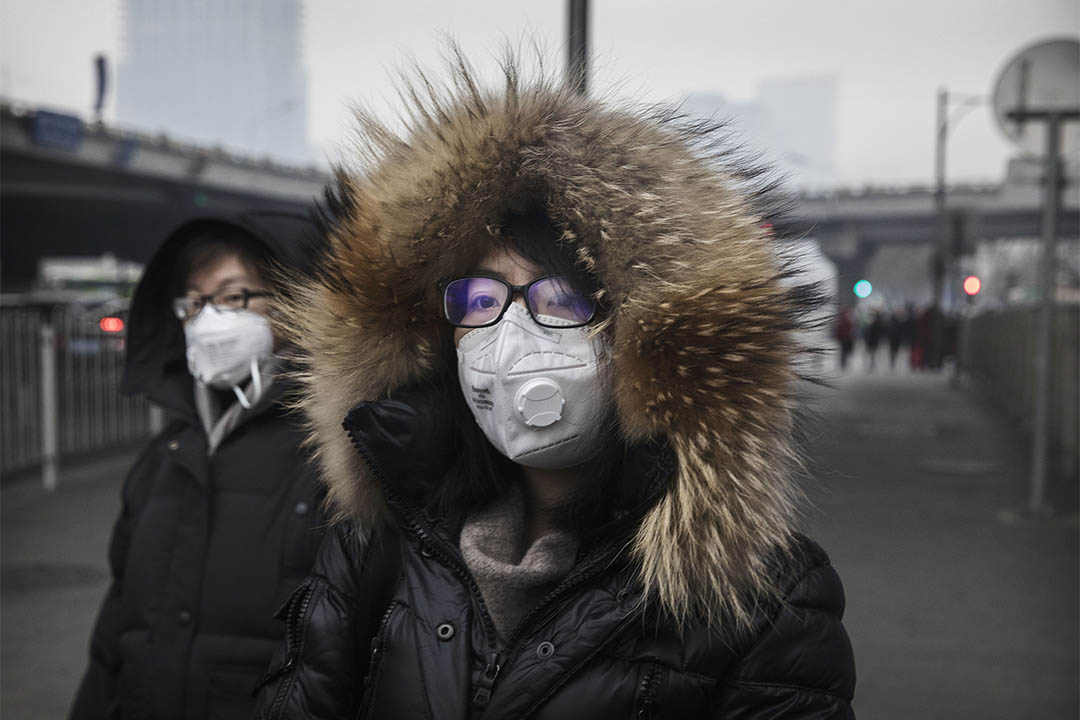 BEIJING, CHINA - DECEMBER 12: Chinese women wear masks as they walk in the street on a polluted day on December 12, 2016 in Beijing, China. As a result of industry, the use of coal, and automobile emissions, the air quality in China's capital and other major cities is often many times worse than standards set by the World Health Organization. (Photo by Kevin Frayer/Getty Images)