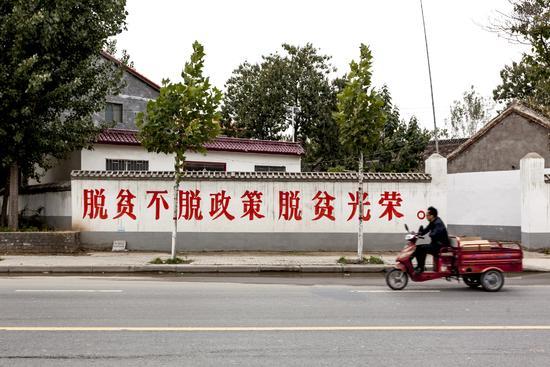 扶贫宣传标语在中国农村随处可见。图为2016年10月30日,河南省兰考县街头的标语。/视觉中国