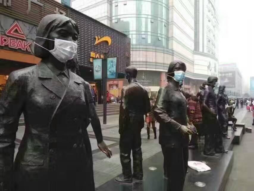 有活动参与者给雕塑戴口罩,希望引起政府关注。(志愿者提供/记者乔龙)