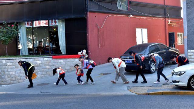 为了躲避摄像头,邓玉峰和几名参与者在幸福大街上弯腰前行。
