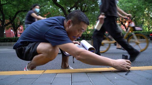 邓玉峰通过测距仪测量路面长度。