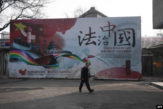 一名保安走过法治中国的广告牌。(2018年3月13日)