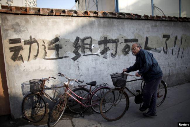 资料照:一名男子骑车走过上海街头一处拆迁地。(2010年12月1日)