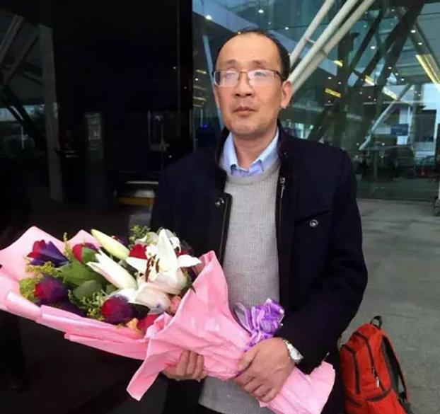 2016年老木回国在机场的照片,手中捧着他妹妹献上的鲜花(网络照片)