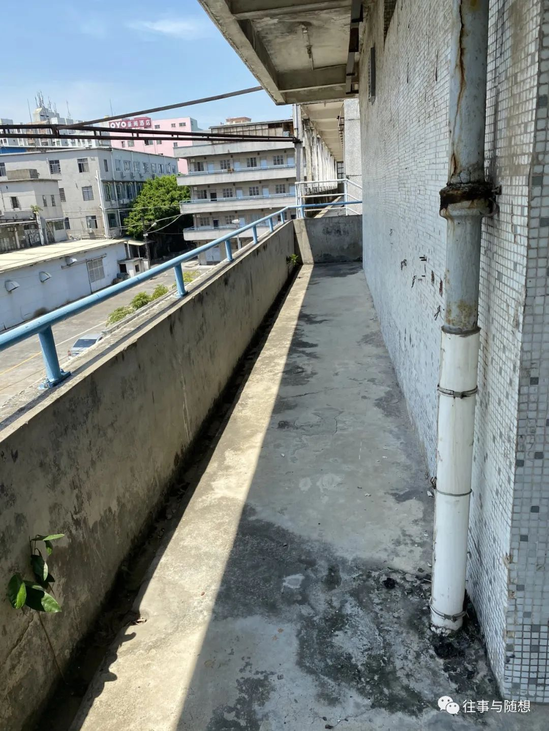 A decrepit concrete walkway with metal railings on the third floor of the dormitory building