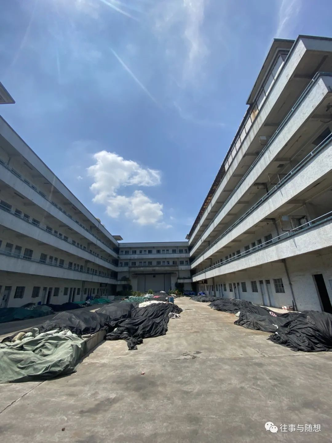 Under a bright blue sky, a rectangular courtyard surrounded by four-story concrete building. The courtyard is heaped with debris covered with green and black tarps.