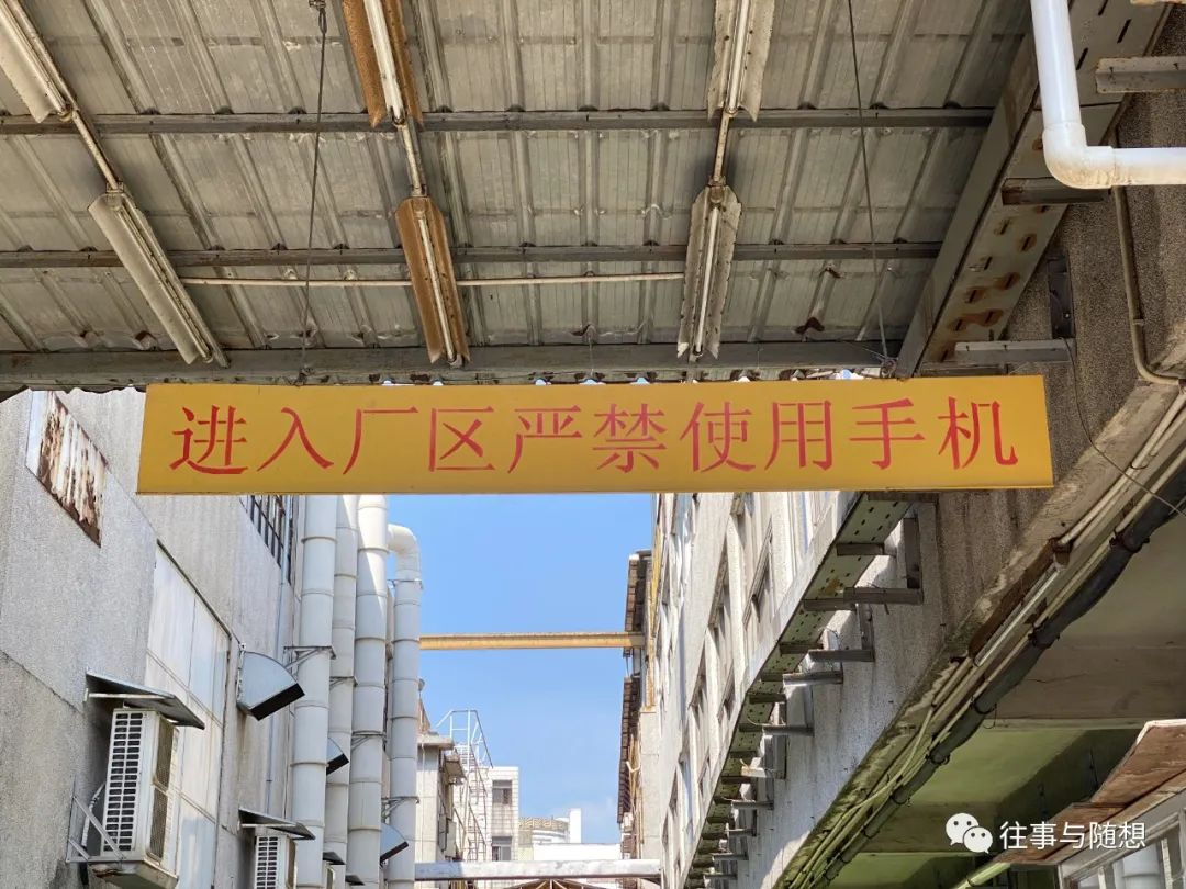 In a breezeway between two factory buildings, a large yellow overhead sign with red Chinese characters cautions that cell phone use is prohibited on factory premises.