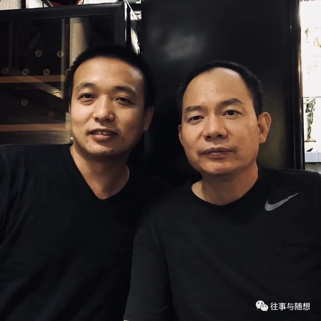 Close-up photo of two men with short, black hair and wearing black t-shirts