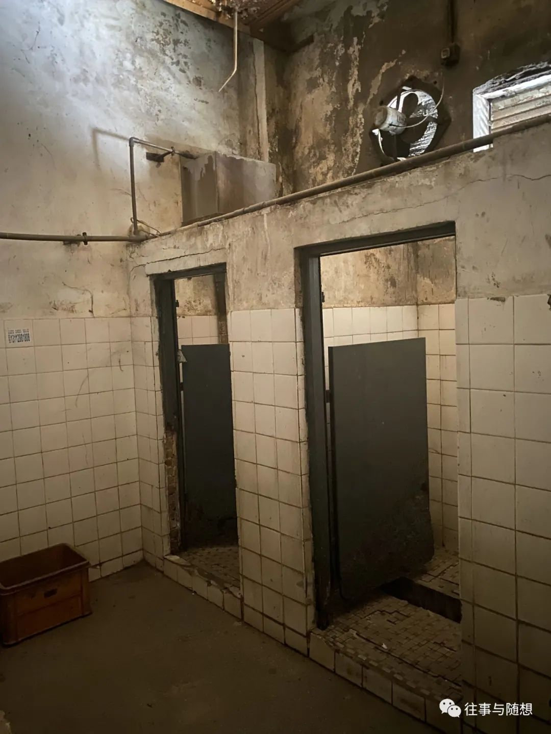 The interior of a very dirty and decrepit men's room with stained white tile, peeling walls and two squat toilet stalls with low wooden doors
