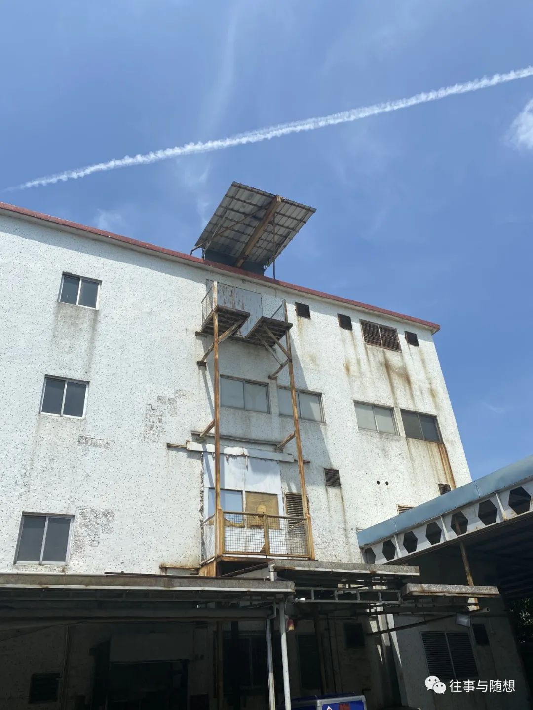 The stained white exterior of a four-story factory building, with a blue sky and white contrail overhead