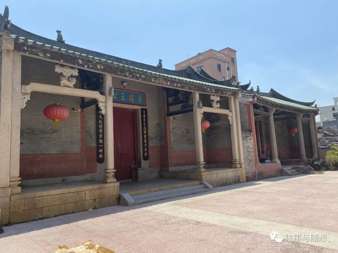 Exterior of a traditional Chinese one-story brick building with tiled roof, red lanterns, decorative pillars and a red door adorned with Chinese calligraphic signs