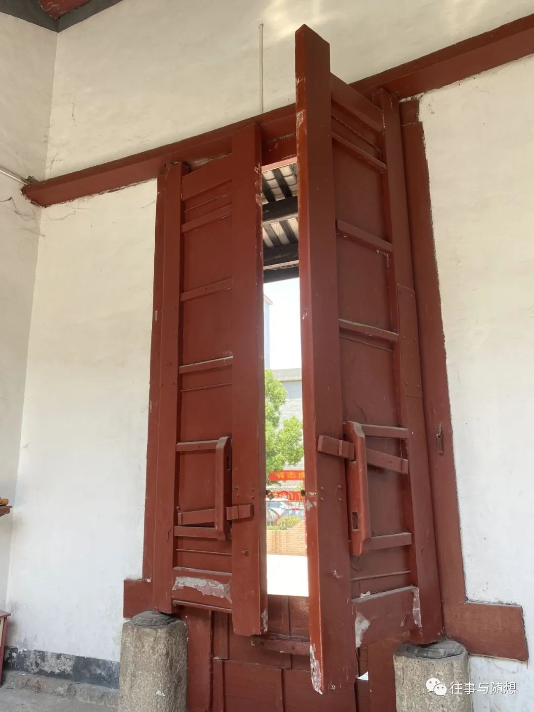 A very tall, red Chinese style wooden door, set into a white wall