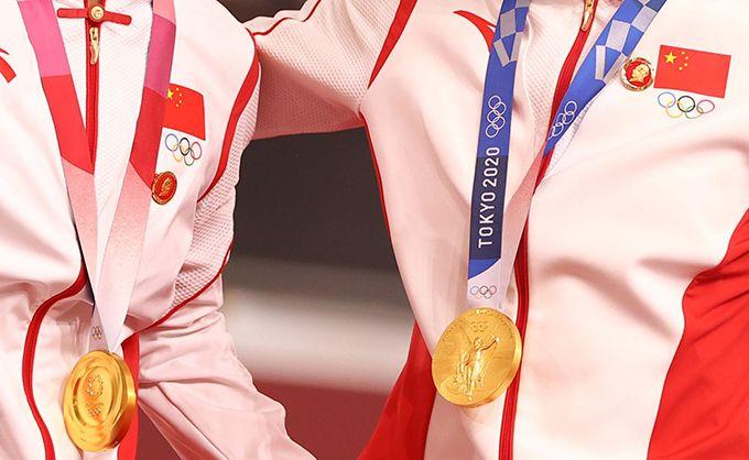 获得东京奥运金牌的中国运动员佩戴毛泽东像章参加颁奖仪式(路透社)