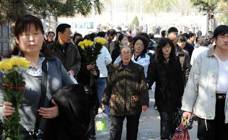 People are walking to a cemetery in the west of Beijing on Friday, April 4, 2008. The Chinese traditional Qingming Festival falls on Friday this year, which is the occasion for Chinese people to pay respect to past ancestors by cleaning their graves, presenting offerings of food, and burning joss paper. [Xinhua]