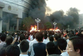 Rioters watch a public building go up in flames in Weng\'an county, Guizhou Province