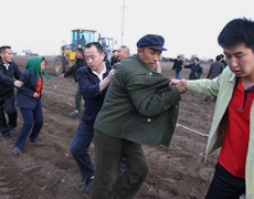 A protester is dragged away from an industrial park, the site of a 2006 land dispute. (AP/CHINA OUT)