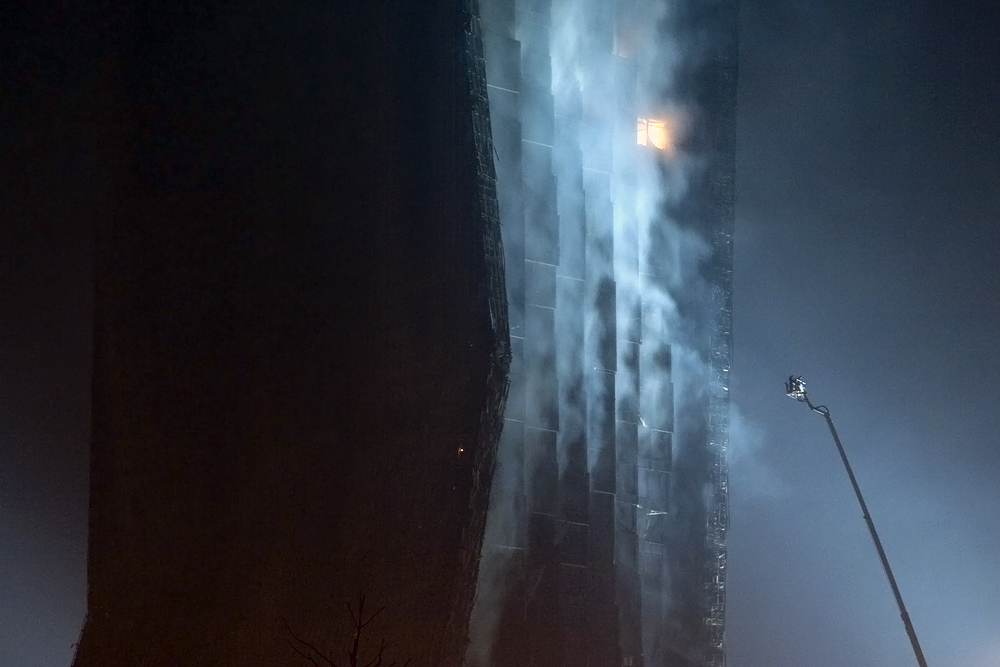 Firefighters spray the CCTV complex blaze from a giant ladder.