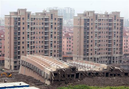 A nearly-finished 13-storey building in Shanghai lies on its side after tipping over, foundations exposed (Reuters).