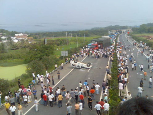 Hundreds of people block the main roads and overturn police cars in Nankang in protest over new tax policy.