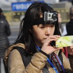 March 3, Beijing: A female journalist with a camera strapped to her head and one hanging around her neck uses her cell phone to report on the Two Sessions.  (NetEase)
