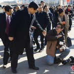 The afternoon of March 4, the first preparatory meeting of the 12th NPC is held. By the eastern gate of the Great Hall, photojournalist Liu Jian trips and falls while reporting for the China Youth Daily; Shaanxi Party Secretary Zhao Zhengyong extends a hand to help him up. (ChinaNews)