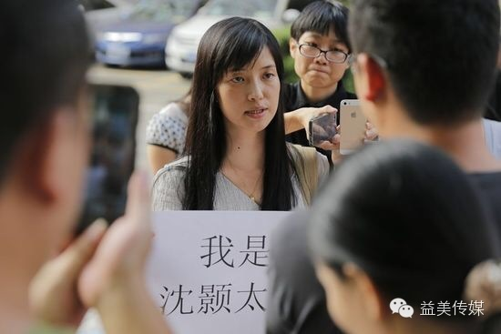 Shen Hao's wife Jiang Hua stands outside of the Southern Media Group building.