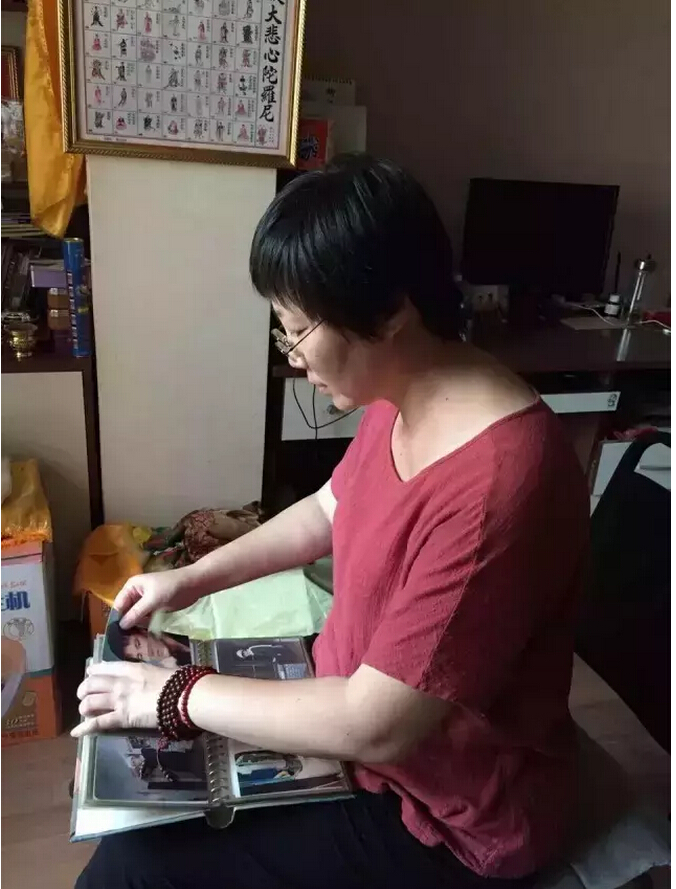 When she misses her husband, Meng Qun looks through old photographs. The only jewelry she wears is a string of dark red prayer beads.