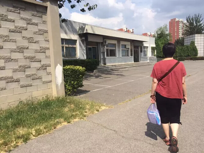 Meng Qun visits the detention center to bring clothes to her husband.