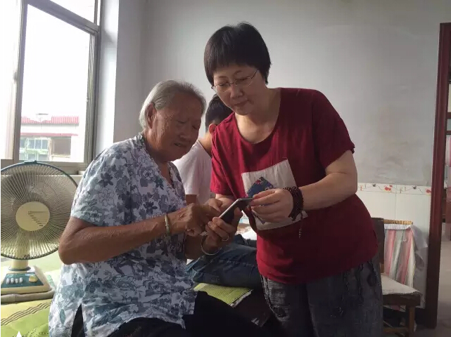 Meng Qun shows family photos on her cell phone to her husband's mother.