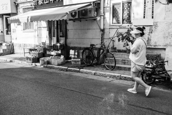 Black and white image of a woman dressed in light shorts, a t-shirt and a sun hat, texting while she walks down a narrow lane in Qingdao. Along the sidewalk are bicycles and a small shop displaying crates of fruits and vegetables.