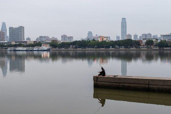 Man fishing in lake against urban skyline