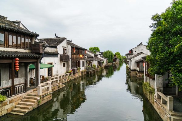 A canal in the ancient town of Dangkou, Jiangsu Province. Both sides of the canal are lined with traditional two-story white houses with verandas, wooden windows and black-tiled roofs.