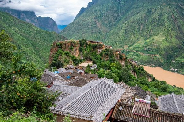 A bird's eye view of the tile-roofed houses of Baoshan Stone Village in Yunnan Province, southwestern China. The houses descend along the ridge of a mountain; in the distance are more verdant mountains, a muddy river, low clouds and a spot of blue sky.