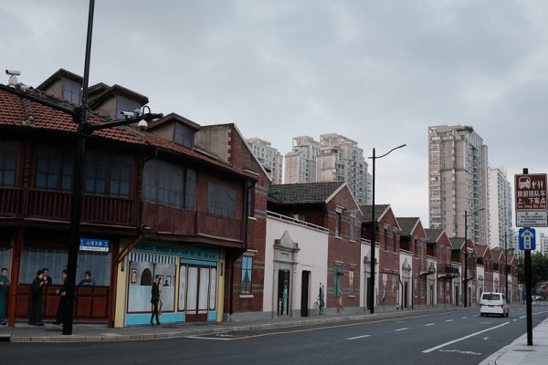 Street view of a row of older two-storey brick and wood buildings, decorated with murals, along Shanhaiguan Lu (Shanhaiguan Road) in Shanghai. Behind them are a number of modern, concrete high-rise apartment buildings.