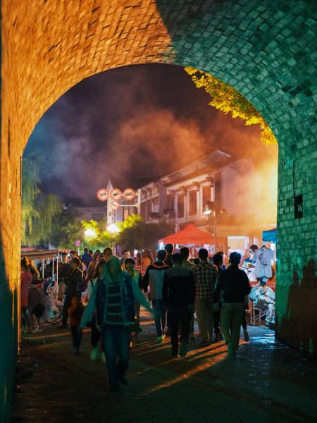 Evening scene of crowds passing through an arched tunnel that is one of the gates of the ancient city wall in the town of Dali, Yunnan Province. Beyond the tunnel are numerous stalls selling clothing and food; yellow and orange lights reflect off the smoke that fills the air.