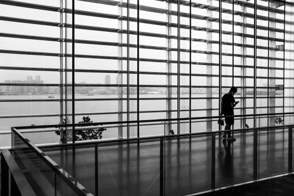 Black and white image of a passenger walking in an empty airport terminal, against floor to ceiling windows that look out on the ocean.