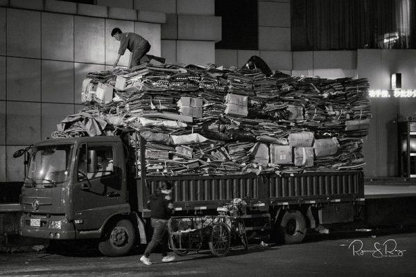 Men load an already heavily laden truck