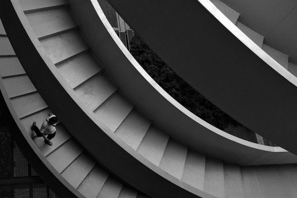 A person, seen from above, walks down a spiral staircase